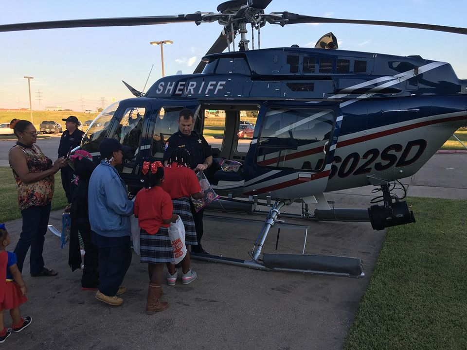 Sheriff deputy standing in front of Jefferson County Sheriff's helicopter with civilians.