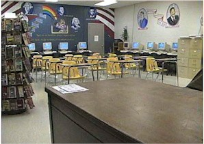 A room with desks, computers, reading materials, and pictures historical figures on the walls.