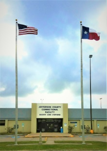 Entrance to Jefferson County Corrections Facility, showing USA flag and Texas flag.
