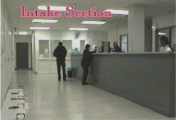 Hallway with workers behind a desk and two people in front of the desk.