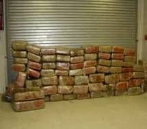 Many packages of marijuana wrapped like bricks stacked against a wall.