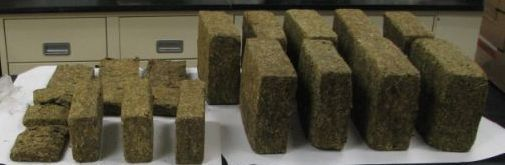 Many bricks of marijuana laid out on a table. Some bricks are large and others are small.