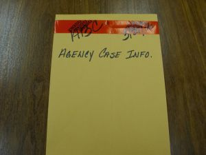 A yellow envelope with red tape seal at the top. ABC, a date, and Agency Case Info is written on the envelope.