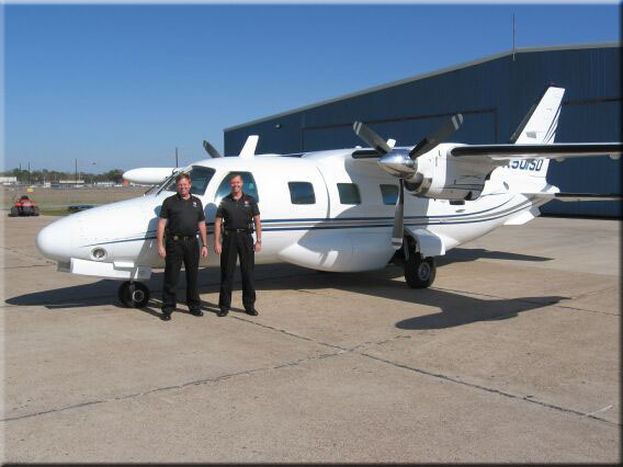Two male officers standing in front of a small airplane.