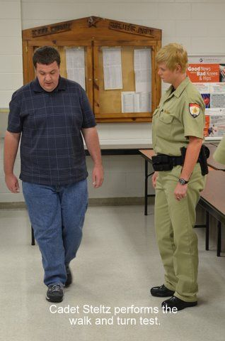 A female cadet watches a man performing a walk and turn test.